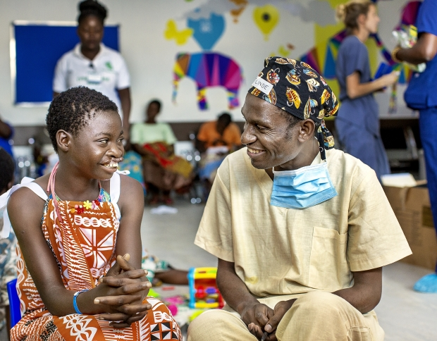 Volunteer surgeon Dr. Tilinde Chokotho speaks with 12-year-old Belita before her surgery during Operation Smile's 2019 mission to Lilongwe, Malawi.